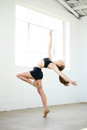 young female dancer wearing black in white-wall warehouse