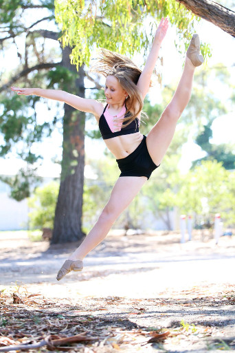 young female dancer wearing black outdoors in park